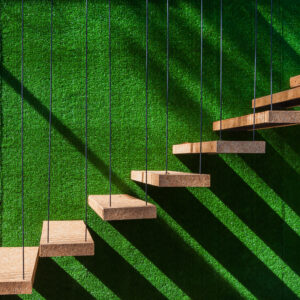 Hanging wooden stairs on artificial grass wall background Apartment staircase made of cables and wood apparently floating.